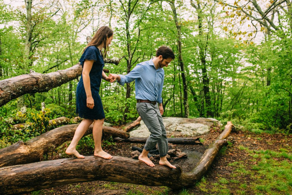 Cold Mountain Engagement Coupe holding hands walking on tree