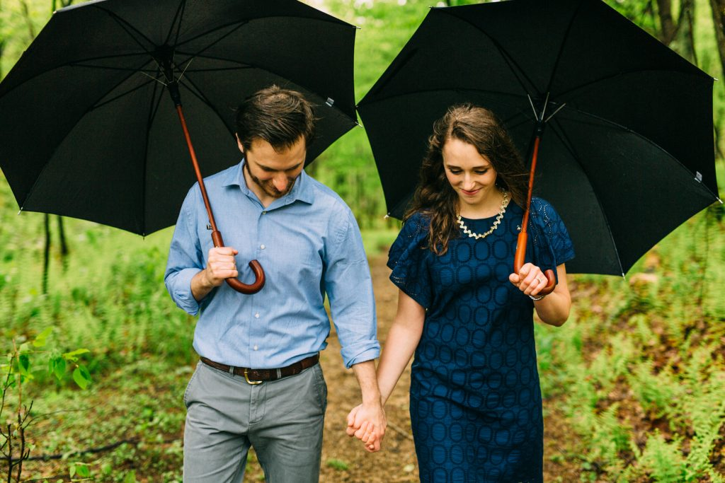 Cold Mountain Engagement Coupe holding umbrellas walking